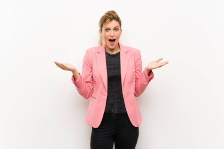 Young blonde woman with pink suit with shocked facial expression Stock fotó