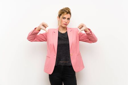 Young blonde woman with pink suit showing thumb down 写真素材