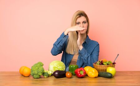 Young blonde woman with many vegetables making time out gesture Stock fotó