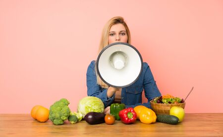 Young blonde woman with many vegetables shouting through a megaphone