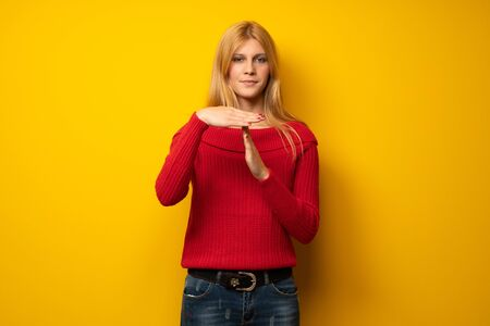 Blonde woman over yellow wall making stop gesture with her hand to stop an act Stock Photo