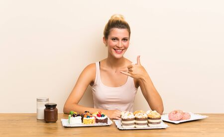 Young woman with lots of different mini cakes in a table making phone gesture Imagens