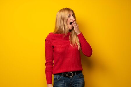 Blonde woman over yellow wall yawning and covering wide open mouth with hand