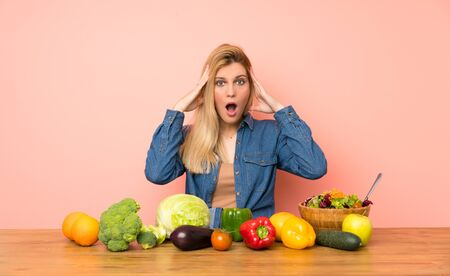 Young blonde woman with many vegetables with surprise expression Stock fotó - 130162866