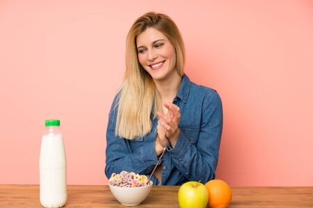 Young blonde woman with bowl of cereals applauding