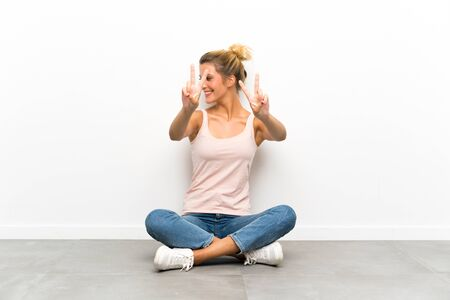 Young blonde woman sitting on the floor smiling and showing victory sign