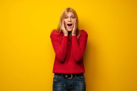 Blonde woman over yellow wall shouting and announcing something