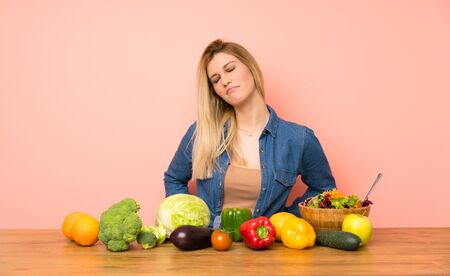Young blonde woman with many vegetables suffering from backache for having made an effort