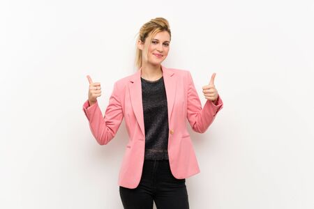 Young blonde woman with pink suit with thumbs up gesture and smiling