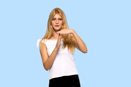 Young blonde woman making stop gesture with her hand to stop an act on isolated blue background Stock fotó