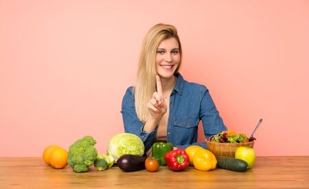 Young blonde woman with many vegetables showing and lifting a finger Zdjęcie Seryjne