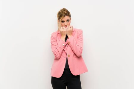 Young blonde woman with pink suit nervous and scared putting hands to mouth