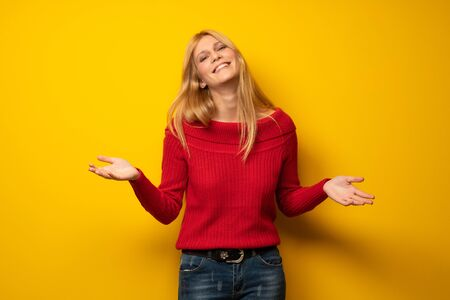 Blonde woman over yellow wall smiling