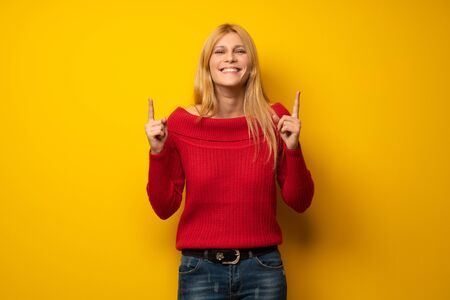 Blonde woman over yellow wall pointing with the index finger a great idea Stock Photo