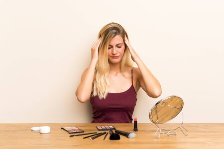 Young blonde woman with cosmetic in a table unhappy and frustrated with something. Negative facial expression