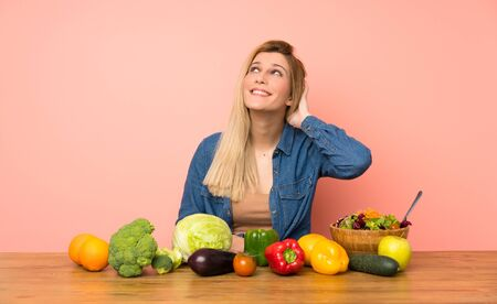 Young blonde woman with many vegetables thinking an idea Stock fotó
