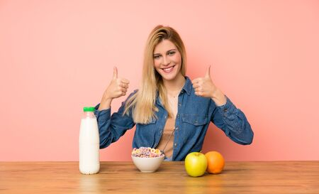 Young blonde woman with bowl of cereals giving a thumbs up gesture Zdjęcie Seryjne