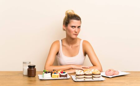 Young woman with lots of different mini cakes in a table having doubts and with confuse face expression Stock fotó