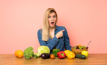 Young blonde woman with many vegetables surprised and pointing side