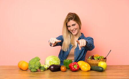 Young blonde woman with many vegetables points finger at you while smiling