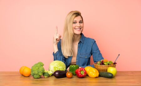 Young blonde woman with many vegetables showing and lifting a finger in sign of the best
