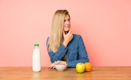 Young blonde woman with bowl of cereals thinking an idea Stock fotó