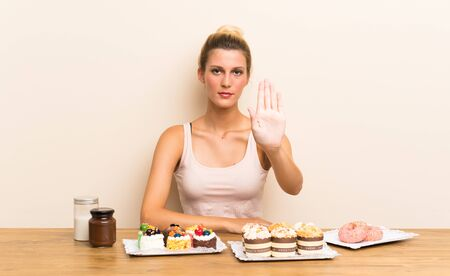 Young woman with lots of different mini cakes in a table making stop gesture with her hand