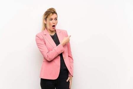 Young blonde woman with pink suit surprised and pointing side