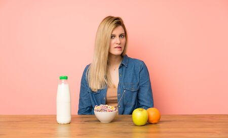 Young blonde woman with bowl of cereals having doubts and with confuse face expression
