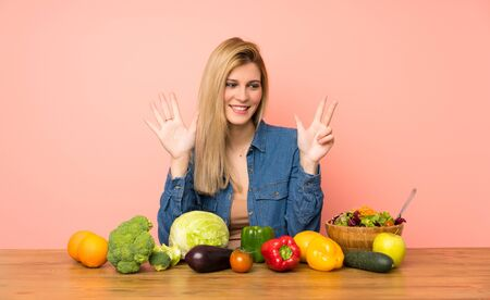 Young blonde woman with many vegetables counting eight with fingers Zdjęcie Seryjne