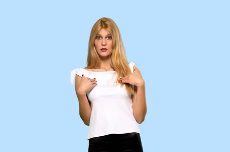 Young blonde woman with surprise facial expression on isolated blue background Stock fotó