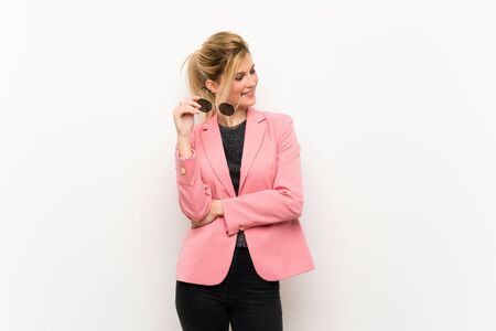Young blonde woman with pink suit with glasses and happy Stock fotó