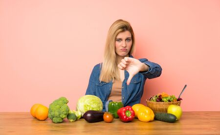 Young blonde woman with many vegetables showing thumb down with negative expression 写真素材