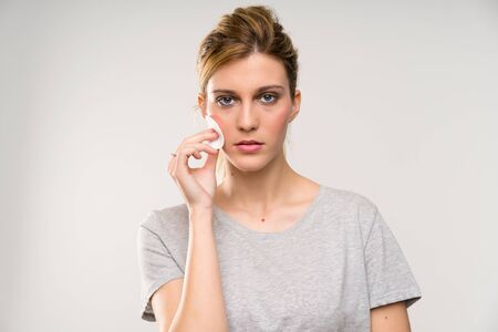 Young blonde woman removing makeup from her face with cotton pad Stock Photo