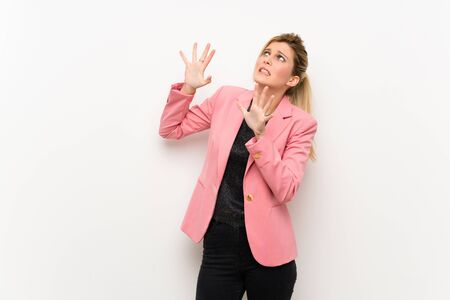 Young blonde woman with pink suit nervous and scared Stock fotó