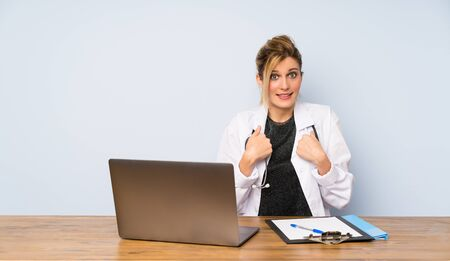 Blonde doctor woman with surprise facial expression Stock fotó