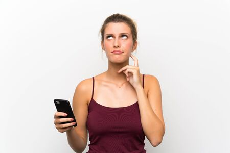 Young blonde woman using mobile phone thinking an idea