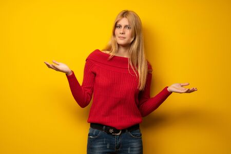 Blonde woman over yellow wall unhappy and frustrated with something because not understand something Stock Photo