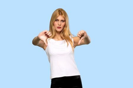 Young blonde woman showing thumb down sign with negative expression on isolated blue background