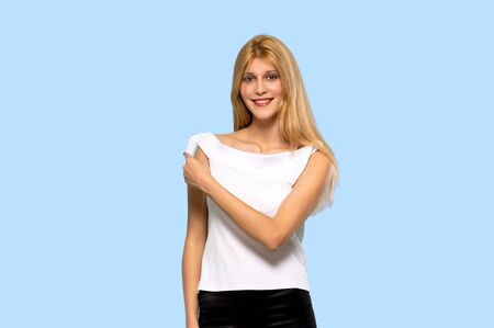 Young blonde woman pointing to the side to present a product on isolated blue background
