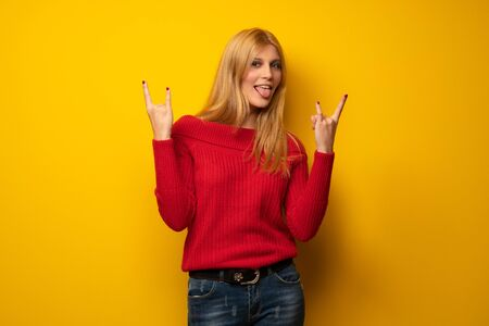 Blonde woman over yellow wall making rock gesture