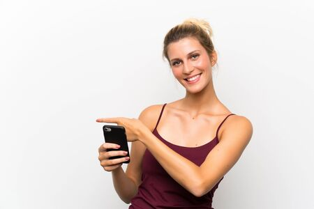 Young blonde woman using mobile phone pointing finger to the side Stock fotó