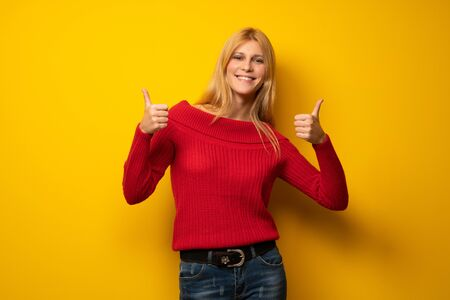 Blonde woman over yellow wall giving a thumbs up gesture with both hands and smiling Stock Photo