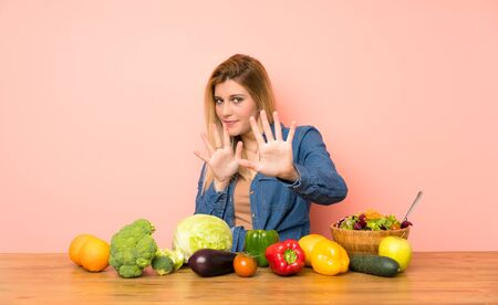Young blonde woman with many vegetables nervous stretching hands to the front