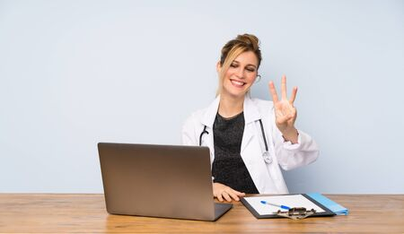 Blonde doctor woman happy and counting three with fingers Zdjęcie Seryjne