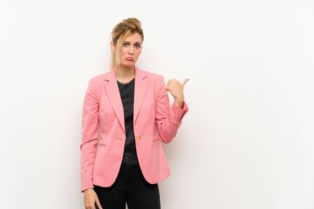 Young blonde woman with pink suit unhappy and pointing to the side Stock fotó