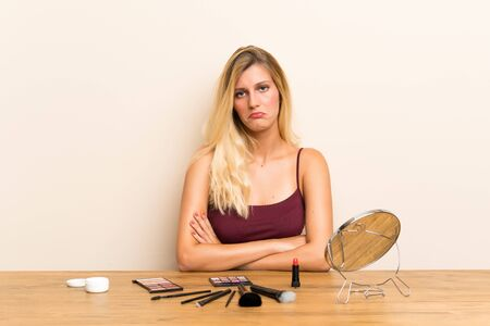 Young blonde woman with cosmetic in a table sad