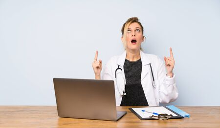 Blonde doctor woman surprised and pointing up Stock fotó