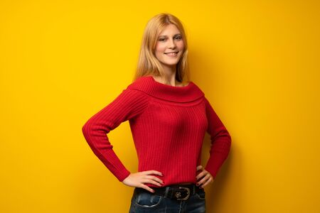 Blonde woman over yellow wall posing with arms at hip and smiling Stock Photo
