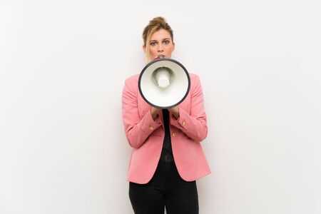 Young blonde woman with pink suit shouting through a megaphone Imagens